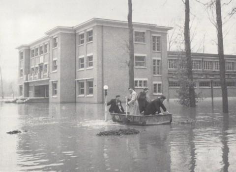 """Op 5 maart 1947 steeg het niveau van de Dijle abnormaal hoog als gevolg van een dag en een nacht onverwacht sterke dooi. De Leuvense binnenstad dreigde te overstromen en men beperkte via de sluizen van """"De Spuye"""" het debiet dat de stad binnen mocht. Met de aldus veroorzaakte opstuwing liet men dus bewust de Dijlevallei in Heverlee overstromen, om erger te voorkomen. Het Arenbergkasteel en het Sportinstituut (zie foto) hoorden bij de ergst getroffen gebieden."""