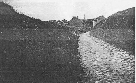 De Hertogstraat liep van de Naamsesteenweg bergop naar het militair oefenterrein. Het was in die tijd niet meer dan een gekasseide holle weg. Op de achtergrond de kerk van Heverlee. (foto rond 1950)